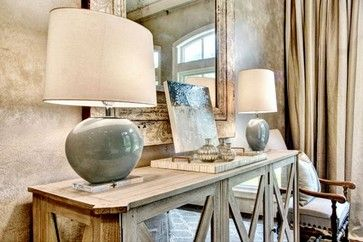 In the dining room, above a white washed buffet is a large oversized mirror flanked by two blue ceramic lamps.