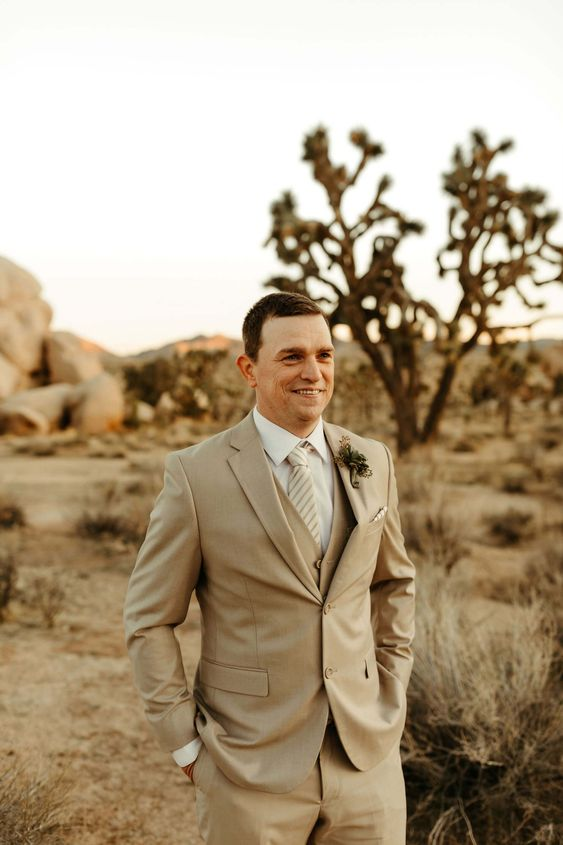 Groom in casual beige suit and striped tie and succulent boutonniere. Click to see more from this boho wedding! #joshuatreewedding #elopement #beigesuit