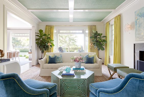 Chartreuse, navy, aqua, and white in East Hampton by Anna Burke Interiors - love the beefy glossy lacquered white moulding, aqua grasscloth ceiling + white walls, blue velvet chairs, chartreuse silk drapes, comfy roll arm linen slipcovered sofa with colorful pillows, fig trees, x stools, abstract art above the mantel, natural rug - LOVE!: