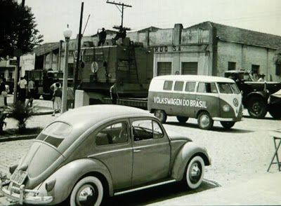 """Antigos Verde Amarelo: Fábrica Volkswagen do Brasil , anos 50 ...Acima, a carreta vai movendo com cautela o pesado maquinário que será instalado na primeira planta da Volkswagen fora da Alemanha, em São Bernardo do Campo -SP. Enquanto isso, a Kombi vai dando retaguarda, e o elegante besouro, calçado com vistosos pneus faixa-branca, vai acompanhando a empreitada. Certamente a """"peça"""" está vindo do porto de Santos -SP."""