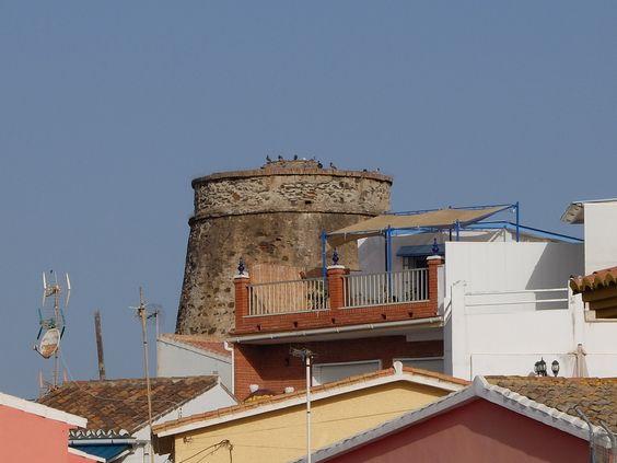Chilches. La torre  sobre y entre  los tejados de viviendas cercanas-
