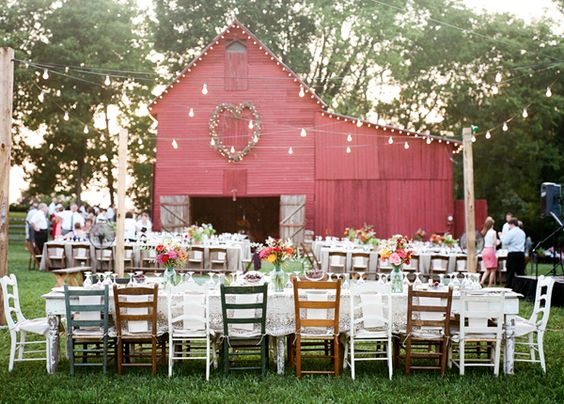 Beautiful wedding venue: vintage red barn with mismatched vintage chairs and table settings: