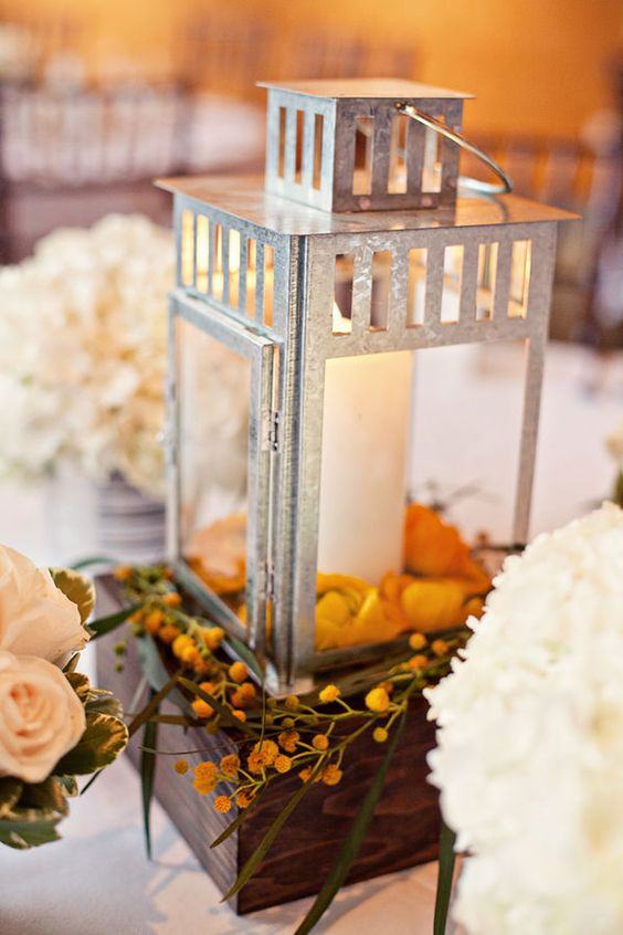Lantern centerpiece with flower petals inside on top of