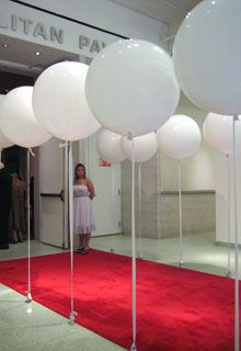 Rows of large, stationary white balloons attached to rigid ribbons and weighted down by silver stars—a play on the museum's...