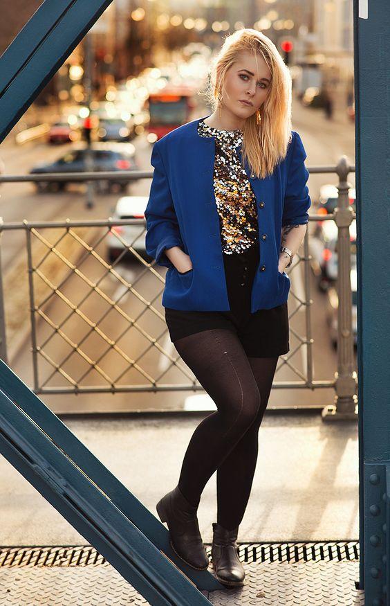 Christina Key trägt eine schwarze Hotpants, einen blauen Blazer und ein glitzerndes Shirt in gold