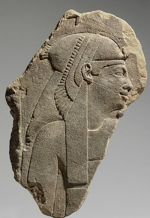 AN EGYPTIAN SANDSTONE RELIEF   PTOLEMAIC PERIOD, CIRCA 2ND CENTURY B.C.   Sculpted in raised relief, preserving a queen or goddess, her face in profile to the right, her torso frontal, wearing a tightly-fitted sheath and a vulture headdress over a long tripartite wig, a lappet falling along the right side of her breast, her face with full lips, a prominent nose, and a protruding chin