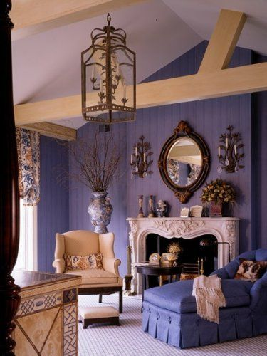 Wisteria colored walls, an antique, inlaid console, white mantle , cream wingback - a beautiful combination.