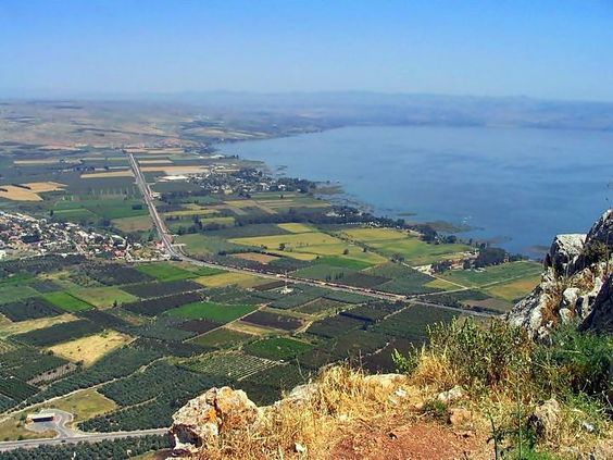 The following photo was taken from the observatory terrace on the top of the cliffs, overlooking the north side of the sea of Galilee. The first two villages are Migdal (center left, where the road bends) and Kibbutz Ginosar (center; on the shore).  Just above that, in the background on the beaches of the lake is  the ancient village of Capernaum. Further to the east is where the Jordan river flows into the lake, and in its background and along the right side of the lake are the Golan…