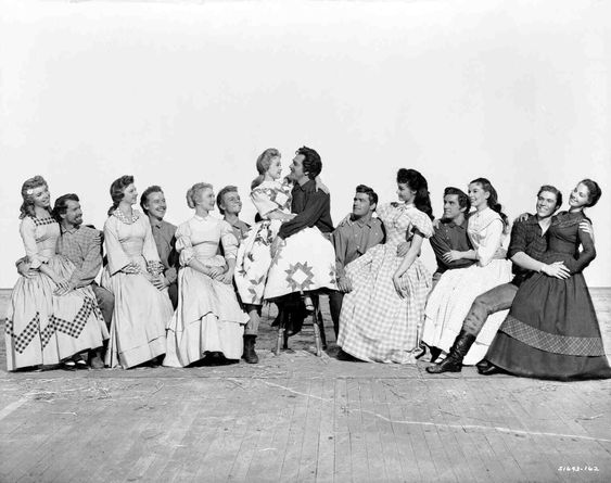 Seven Brides for Seven Brothers (Full publicity shot of women sitting on laps of men, L to R: Ruta Lee as Ruth, Matt Mattox as Caleb, Norma Doggett as Martha, Marc Platt as Daniel, Nancy Kilgas as Alice, Russ Tamblyn as Gideon, Jane Powell as Miily, Howard Keel as Adam, Jeff Richards as Benjamin, Julie Newmar as Dorcas, Tommy Rall as Frank, Betty Carr as Sarah, Jacques D'Amboise as Ephraim and Virginia Gibson as Liza)