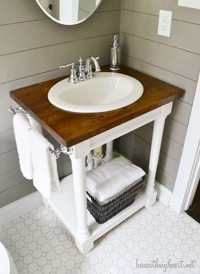 This small woodworking project used four standard newel posts for the vanity's ornate legs. The open design includes a low plywood shelf, delicate trim details made from molding, and a stained butcher-block top that was cut with a jigsaw to fit a recessed sink.