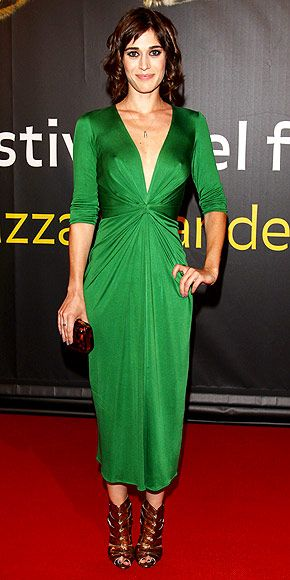Lizzy Caplan mixes elegance with edge in this plunging, emerald green  Issa London dress at the Locarno, Switzerland film festival.    The star of the upcoming film, Bachelorette added cut-out, Brian Atwood peep-toe booties and a reptilian printed clutch to complete her bold look.
