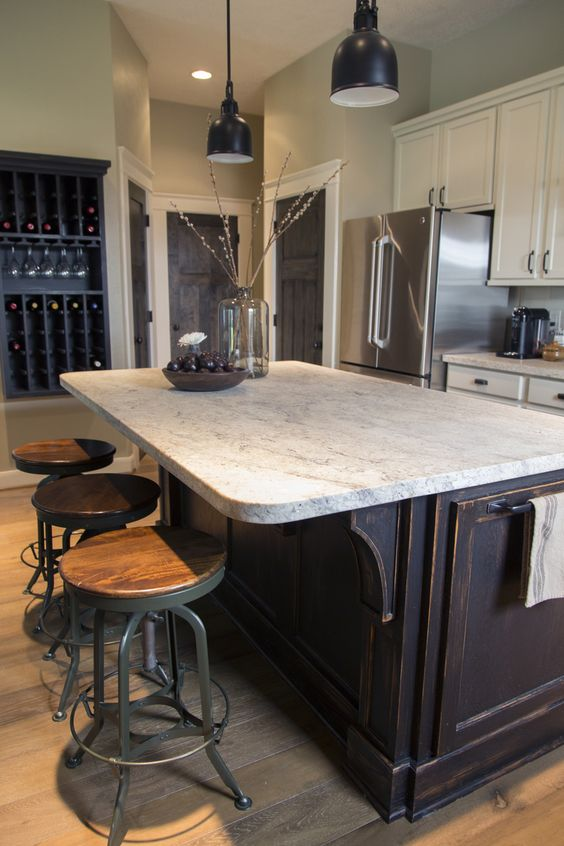 The dark wood of this island looks great topped with a thick slab of granite. It also helps to downplay the elegance of the piece as well with its own rustic appearance.
