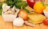 Vegetarian lasagna ingredients on wooden background