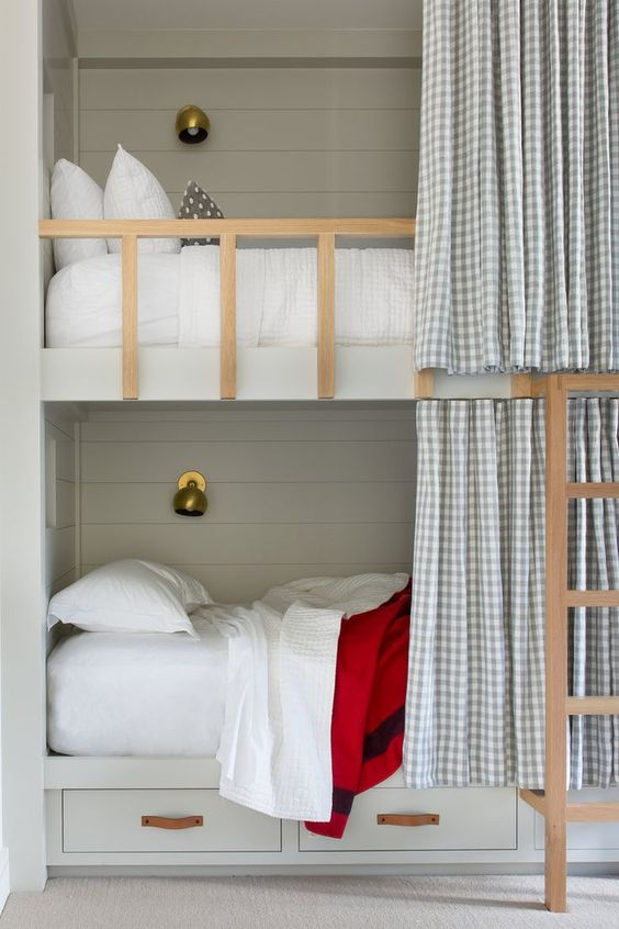 Built in bunk beds in a khaki color with shiplap + leather hardware on the drawers + brass sconces. We love the option for more privacy with the curtain pullback | ABD Studio