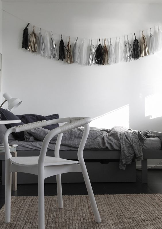 The of the aquarius blog. Bedroom in shades of grey with playful decoration in the wall: tassels in white, black, silver and gold