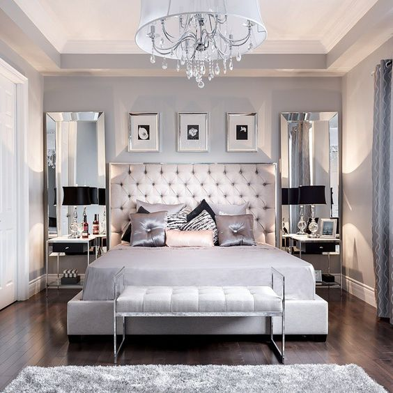 This gray bedroom is elegant and stylish with the tufted headboard and chandelier. It also has mirrors and plenty of black and silver to accent the gray itself to create this ideal look.