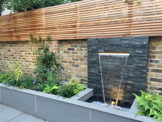 Contemporary LED lit water blade with slate walling and slatted trellis
