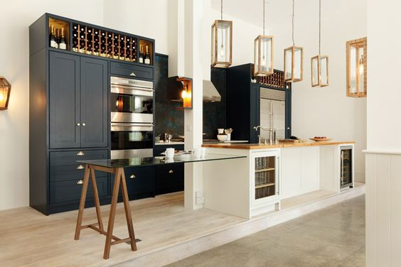 Reclaimed Victorian era floorboards and funky box lights give this kitchen an edgy style. The mixed materials combined with hand-painted tulipwood cabinetry, glass cantilevered breakfast bar and slick contemporary Sub-Zero and Wolf appliances results in a well-heeled contemporary style kitchen. Bovingdon range kitchen by Cue & Co of London hand-painted in Farrow & Ball Hague Blue and Strong White paint. Made in Parsons Green, London. cueandco.com utopiamag.co.uk #modernbritish #kitchen