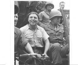Lt Gen. George S. Patton sits in a jeep surrounded by grateful Frenchmen and GI's of his command near Coutances. 29/07/44 = [Assis dans sa jeep, le général George S. Patton est entouré de civils venus le saluer].