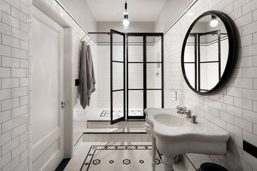 Industrial farmhouse style bathroom with pedestal sink, black shower doors, and subway tile.