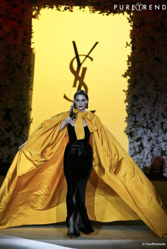 Yves Saint Laurent : a dramatic yellow cape and Le Smoking black velvet dress (made famous by Nan Kempner) worn by Carla Bruni during the 2002 YSL finale retrospective.