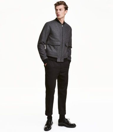 Black. Suit pants in twill with wool content in a slightly looser fit. Side pockets, welt back pockets, and slightly shorter legs and cuffs at hems. Creases