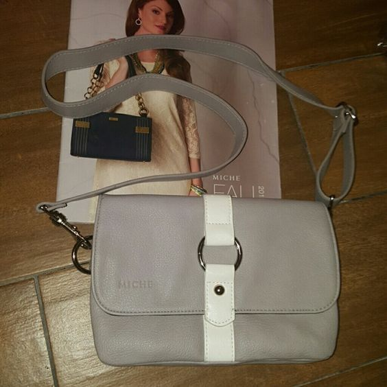 New grey Miche Brand New never used! Grey and white/ can be worn as cross body, around waist, or as a clutch..  Few marks on the backside of the purse on the white stripe (scuffs from being packed away) Refer to last picture. Miche Bags Crossbody Bags