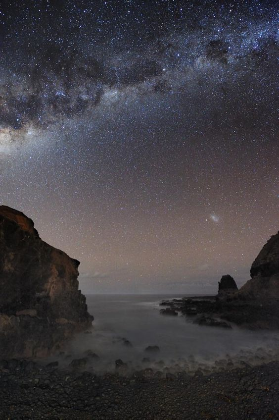 July 2010 The Milky Way Over Pulpit Rock Credit  Copyright: Alex Cherney (Terrastro) This image tkn only last month fr Cape Schank, Victoria, Australia. The frame is highlighted by a dreamlike lagoon, 2 galaxies,  10s of 1000s of stars. The rock cropping on the left may appear fr this angle like a human head, but the more famous rock structure is on the far right  known as Pulpit Rock. On the right, just abv Pulpit Rock, is the Milky Ways small neighboring galaxy t