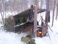 This is how to set up a backwoods camp. I might add an additional tarp to one of the sides to cut down on wind.