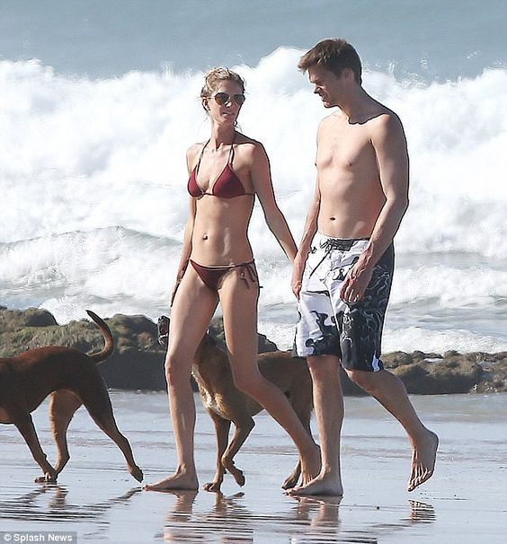 Beauty on the beach: Gisele displayed her perfect bikini body as the two strolled hand-in-hand