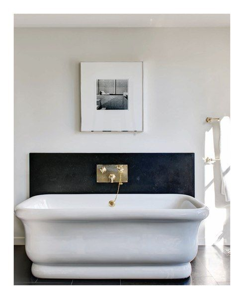 My bathroom - white zellige tiles on wall behind tub, VOLA unlacquered brass fittings, freestanding bathtub
