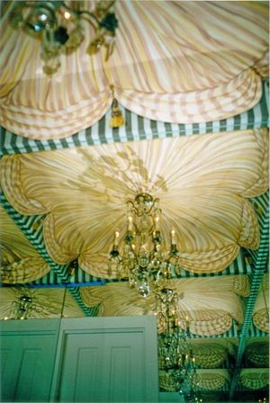 Painted fabric is reflected back in this mirrored powder room.