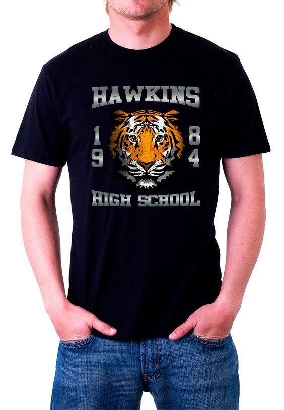 Camiseta Stranger Things logo Tiger Hawkings School. Modelo negro  Espectacular y exclusiva camiseta perteneciente a la popular serie revelación de 2016 titulada Stranger Things con el diseño del logo del tigre de la escuela Hawkings.