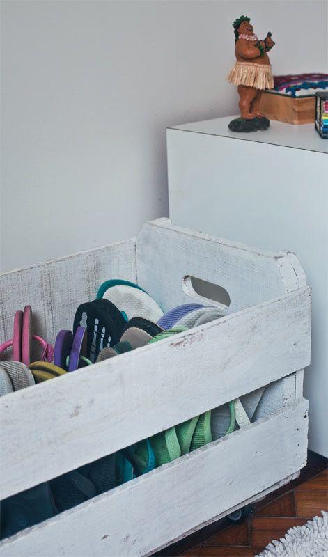 Pintura branca e rodinhas transformaram o caixote de feira em abrigo para a coleção de chinelos.:
