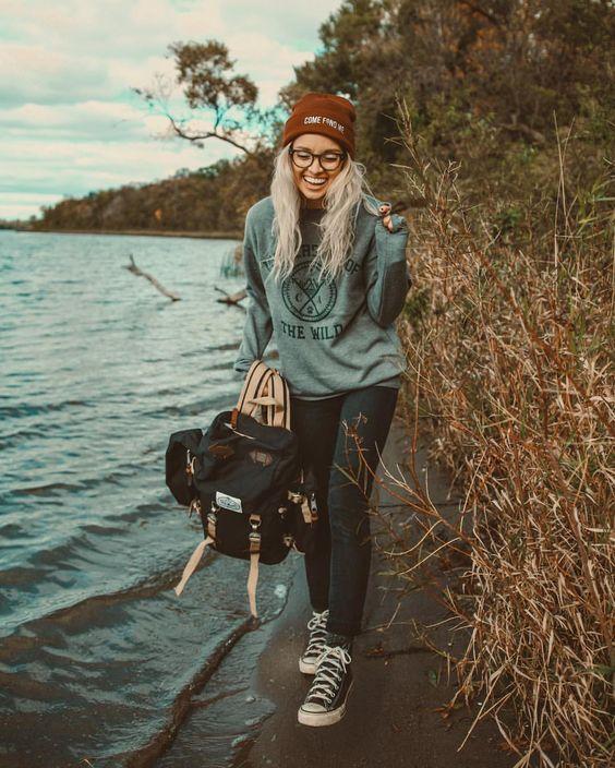 Chica vestida al estilo hipster con gafas, gorro de lana, converse y mochila.