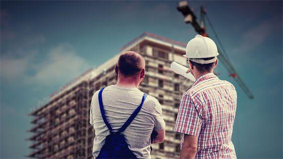 Foto de dois homens de costas olhando para um prédio em construção. Ao lado do prédio, um imenso guindaste. O homem da direita usa um capacete de segurança branco e aponta para o prédio. O da esquerda usa camiseta branca e macacão azul.
