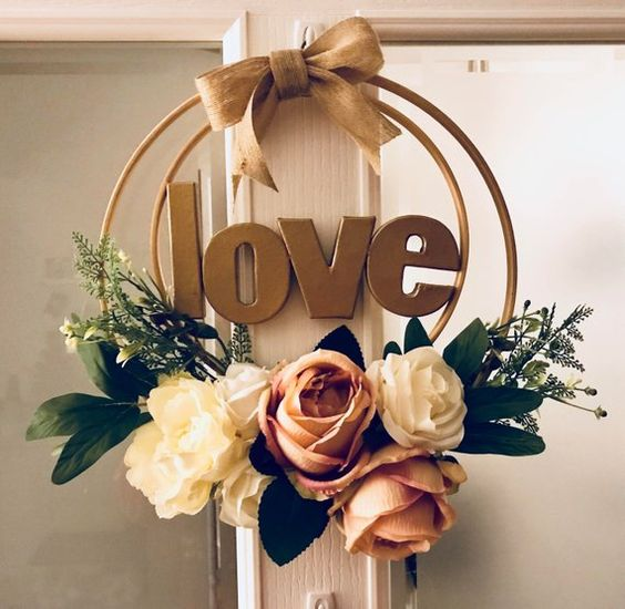 A beautiful artificial flower wreath with LOVE at the centre - Using two wooden embroidery hoops as the base, the largest of which measures 32cm diameter. This particular one has flowers in pinks and creams with gold lettering, but if you have specific colours in mind, I can make it