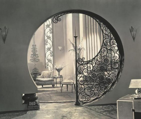 Kind of a blend of geometric Art Deco and the free-flowing curves of Art Nouveau. This was actually a movie set from Pleasure Crazed (1929).