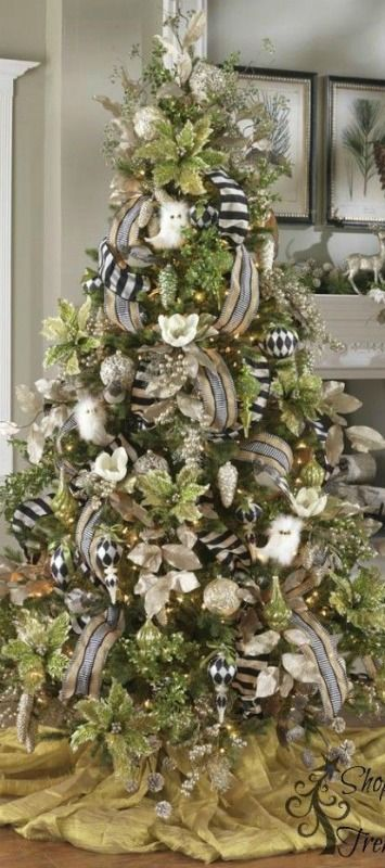 Stunning Christmas Tree | Huge glittered green poinsettias and pearly berry sprays, cream flowers and the white owls really make a statement. Love the black/white harlequin pattern ornaments and the ribbons.: