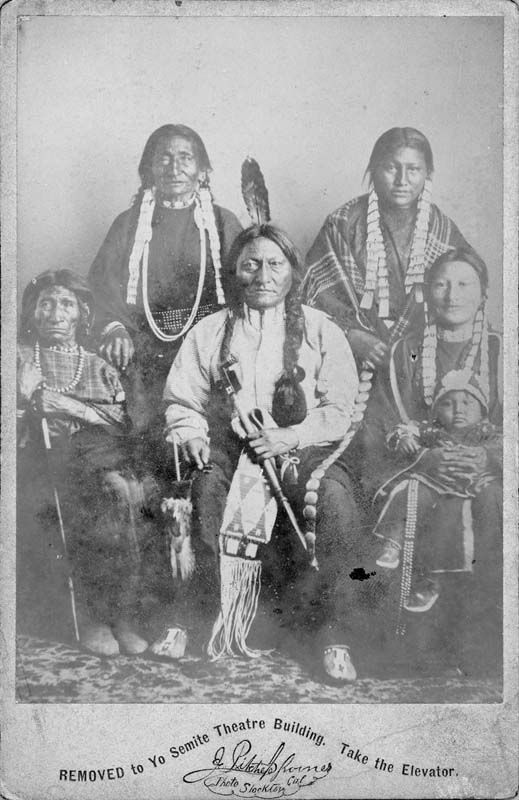 """Portrait of Sitting Bull and his family wearing traditional regalia. Sitting Bull's mother, Her Holy Door sits on his right, wives Four Robes and Seen-By-The-Nation stand behind him, and his oldest daughter, Many Horses and her son sit on his left. Sitting Bull holds a pipe and pipe bag on is lap. Hand written note on verso of card reads, """"Sitting Bull & family, Ta Tonka E U tanki, Sioux.""""  Date: circa 1883"""
