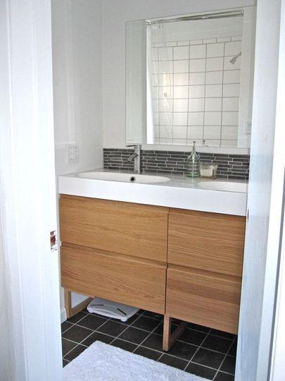 black tiles + wood drawers + white porcelain sink