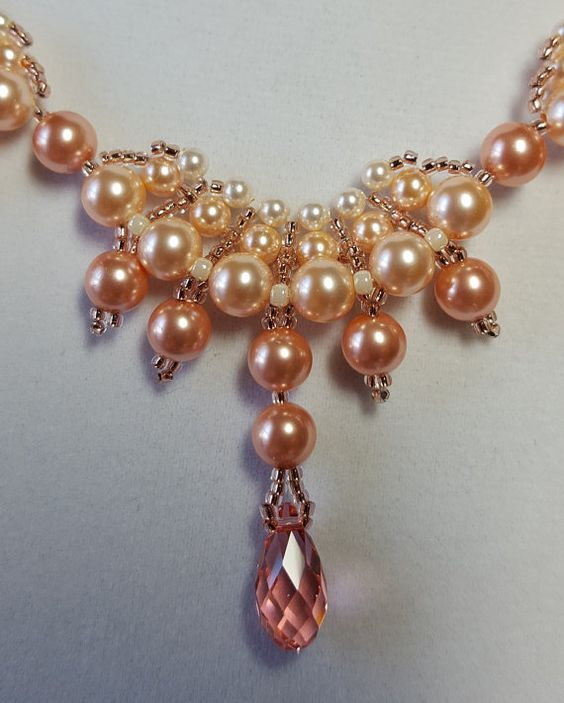 Nine Scallops of Swarovski Peach Pearls and Crystals are woven together to create this stunning statement piece.