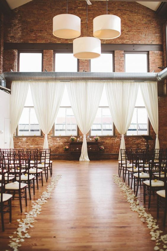 Exposed brick, white curtains, wood floor, pretty petals | Image by The Shalom Imaginative