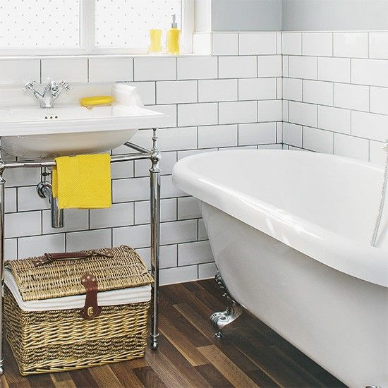 White metro tiles with dark grout give this compact bathroom a real sense of style. The picnic basket is a create storage idea that adds character to the space while splashes of yellow prevent it feeling sterile
