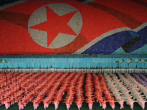 """housands of performers dance in unity at the Arirang Mass Games in Pyongyang, North Korea. In the background, schoolchildren hold colored booklets to create each """"pixel"""" of the nation's flag. The two-month-long festival depicts the story of North Korea through gymnastic and artistic expression."""