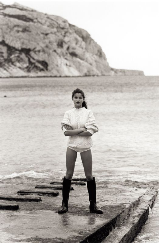 sweater, bathing suit, big boots.  looks like a good beach outfit to me.