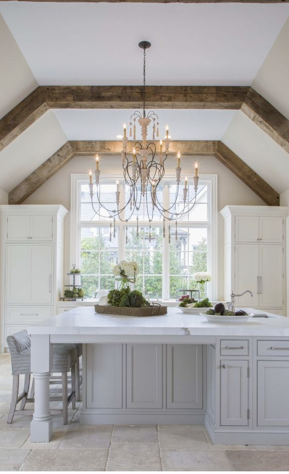 Magnificent and serene kitchen design in this lofty kitchen with natural wood beams at ceiling, romantic French Country chandelier, and symmetry. #frenchcountry #kitchendesign #serene #whitekitchen #whitedecor #chandelier