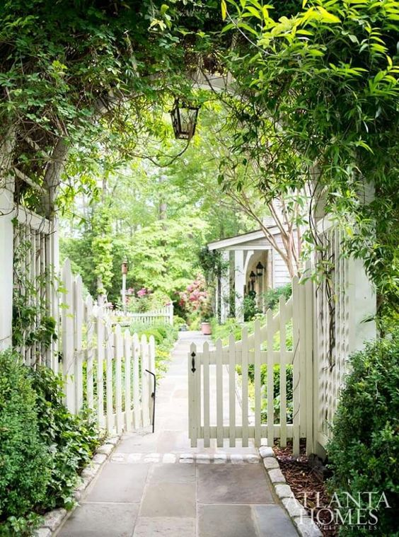 Garden Gate Ideas and Beautiful Gardens to Inspire! White picket fence swinging gates beneath an arbor with climbing vines leading to a lush garden flowering with blooms. #picketfence #gardengate #gardenideas #summerstyle #outdoorliving #landscapeideas
