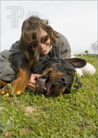 Picture of smiling young womand and her purebred rottweiler
