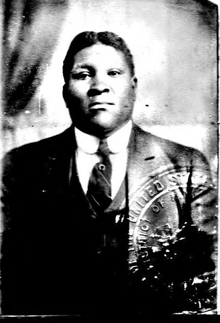Passport photo of Will Garland: a Black man wearing a suit and tie. He has short black hair. He is in a photo studio and you can see a curtain behind him. The image is stamped with the raised US stamp.
